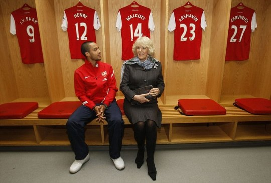 Camilla, Duchess of Cornwall sits in the Arsenal dressing room with Arsenal player Theo Walcott
