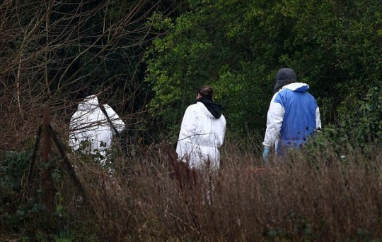Police forensic officers inspect the scene around Reed Pond in Canterbury, Kent