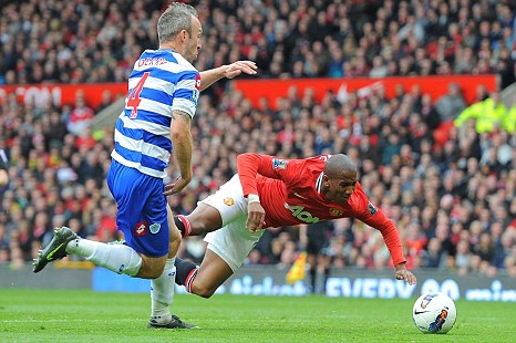Manchester United's English forward Ashley Young is fouled by Queens Park Rangers English midfielder Shaun Derry