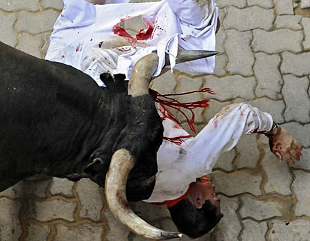 Soiled trousers: A runner is gored by a bull at Pamplona's San Fermin festival