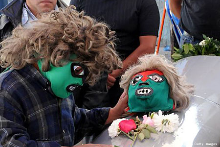 Masks of respect: Relatives say a final goodbye at the twins home in Mexico City