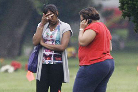 Upsetting: Relatives search for a grave at Burr Oak cemetery. Orange flags mark disturbed plots
