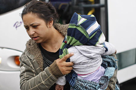 A Romanian woman shields a child as she arrives at a Belfast leisure centre