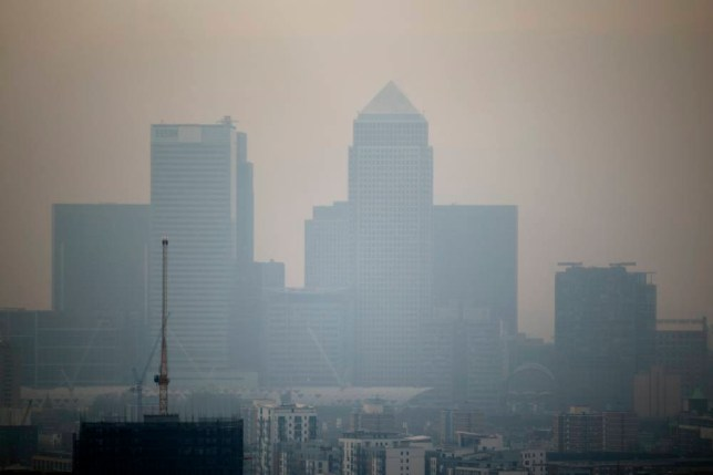 The skyscrapers of the Canary Wharf business district in London are shrouded in smog, as seen from a viewing gallery on the Orbit sculpture in the Queen Elizabeth Olympic Park during an tour of the park organized for the media, Wednesday, April 2, 2014. British authorities have warned people with heart or lung conditions to avoid exertion as a combination of industrial pollution and Sahara dust blankets the country in smog.  The environment department said Wednesday's air pollution level could reach the top rung on its 10-point scale. (AP Photo/Matt Dunham)