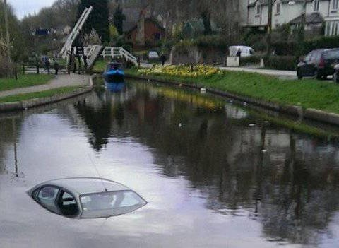 Man parks car next to canal. Man goes to pub. Man comes back to find car in canal