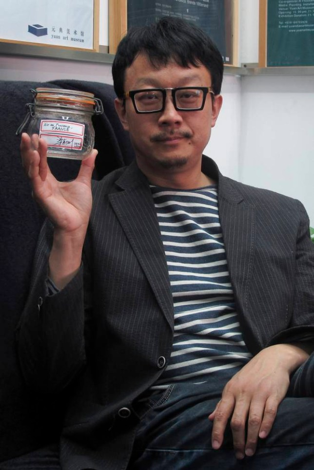 In this April 5, 2014 photo, Beijing artist Liang Kegang poses with the jar of fresh air collected in Provence, France, in an art gallery in Beijing, China. The jar of air has fetched $860 in a small auction as a piece of conceptual art to protest Beijing's choking pollution. (AP Photo/Didi Tang)