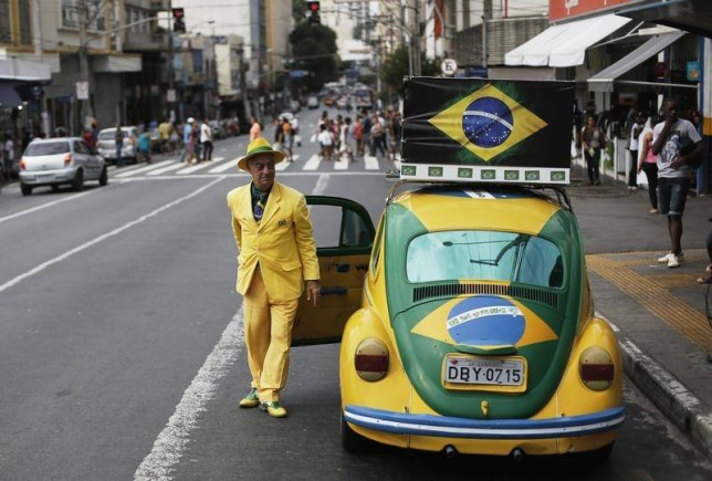 Spot the patriot: Parking one of his two VW Beetles (Picture: Reuters)
