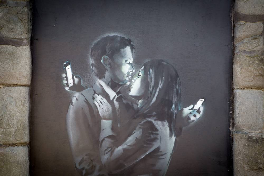 Sign of the times: New Banksy artwork shows a couple checking their mobile phones while embracing (Picture: SWNS)