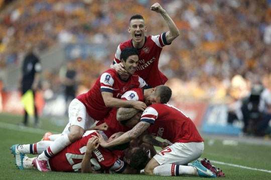 Arsenal players celebrate with Welsh midfielder Aaron Ramsey (ground-obscured) after he scored the third and winning goal during the English FA Cup final match between Arsenal and Hull City at Wembly Stadium in London on May 17, 2014. AFP PHOTO/ADRIAN DENNIS NOT FOR MARKETING OR ADVERTISING USE / RESTRICTED TO EDITORIAL USE ADRIAN DENNIS/AFP/Getty Images