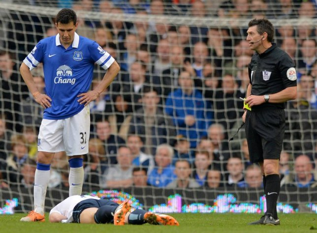Manchester City's Bosnian striker Edin Dzeko (Below L) lies injured as the referee (R) holds the yellow card during the English Premier League football match between Everton and Manchester City at Goodison Park in Liverpool on May 3, 2014. AFP PHOTO / PAUL ELLIS RESTRICTED TO EDITORIAL USE. No use with unauthorized audio, video, data, fixture lists, club/league logos or live services. Online in-match use limited to 45 images, no video emulation. No use in betting, games or single club/league/player publications.PAUL ELLIS/AFP/Getty Images