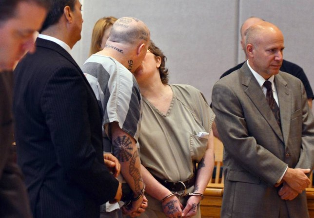 Jeremy Moody, left, kisses his wife, Christine Moody, right, while standing with their lawyers shortly before they were both sentenced to life in prison on Tuesday, May 6, 2014, in Union, S.C. Authorities say Jeremy and Christine Moody killed 59-year-old Charles Parker and his 51-year-old wife Gretchen Parker last July. Investigators said the Moodys are members of a loosely organized online white supremacist group called Crew 41 and decided to kill Parker because he had taken advantage of a disabled woman. (AP Photo/Spartanburg Herald-Journal, Tim Kimzey)