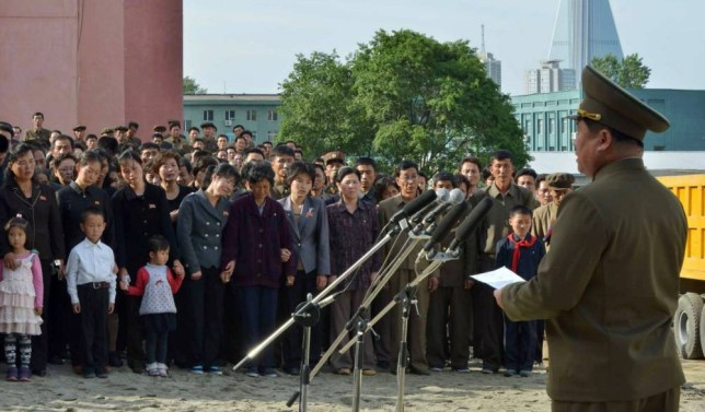 Disaster:  An official apologises to families in Pyongyang where the 23-storey building fell down (Picture: AP)