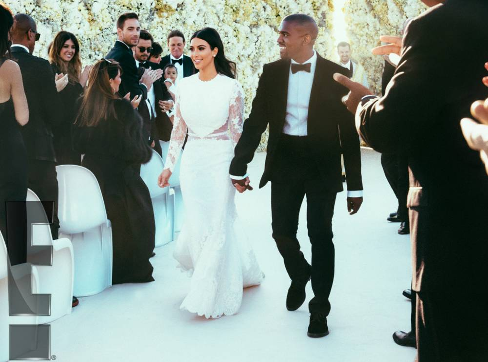 """And now, we would like to present you the first official photos of Kim Kardashian and Kanye West as newlyweds...E! News has obtained the exclusive first look of the married couple after their lavish and out-of-this-world wedding this weekend in Florence, Italy!..As you probably already expected, the duo are absolutely glowing and beaming with love after saying """"I do"""" at the Forte di Belvedere in front of their nearest and dearest. In the first of the exclusive photos, the couple are sharing a newlywed kiss in front of the gorgeous white flower wall erected for the occasion immediately following their vow swap."""