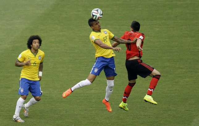Brazil's Marcelo, left, looks on a Brazil's Luiz Gustavo and Mexico's Hector Herrera, right, go for a header during the group A World Cup soccer match between Brazil and Mexico at the Arena Castelao in Fortaleza, Brazil, Tuesday, June 17, 2014. (AP Photo/Themba Hadebe) AP Photo/Themba Hadebe