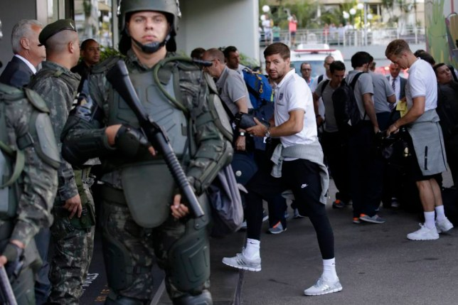 England's national soccer team captain Steven Gerrard, center, and goalkeeper Joe Hart, right, pass members of the Brazilian army standing on guard as the players got off the team coach upon their arrival at the squad's hotel for the 2014 soccer World Cup in Rio do Janeiro, Brazil, Sunday, June 8, 2014.  (AP Photo/Matt Dunham)