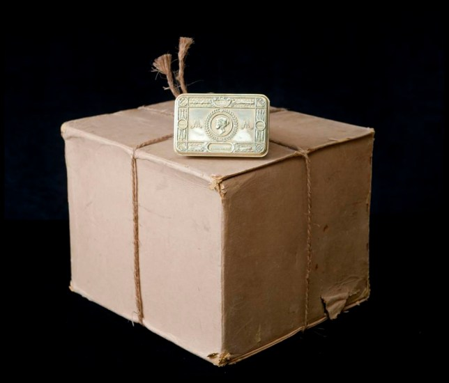 BNPS.co.uk.(01202 558833) Pic: PhilYeomans/BNPS The unopened box with a tin given to auctioneer Patrick Bogue's own father. 100 year old time capsule from Xmas 1914 discovered. A time capsule box of Christmas gifts originally destined for First World War troops fighting in the trenches in 1914 is to be opened for the first time after it emerged for sale. X-rays have shown that the unremarkable brown cardboard box contains 81 brass tins containing gifts for front line soldiers sent from the Royal family. The brass tins held cigarettes, pencils made from shell casings, chocolate, sweets and even Christmas cards. They were made in their thousands then shipped off to soldiers fighting in the trenches over the first Christmas of the Great War. But one box never made it to its intended destination and is now up for sale 100 years on for almost £30,000 after being discovered by a collector. It will be opened for the first time by Lady Emma Kitchener, great-grandniece of military leader Herbert Kitchener, at the Chalke Valley History Festival near Salisbury, Wilts. A select amount of tins will be sold at the festival for £300 with the rest being auctioned at Onslows in Blandford, Dorset, on July 9.