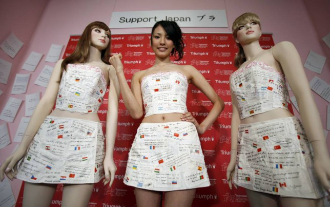 "A model clad in lingerie maker Triumph International's ""Support Japan Bra"", featuring handwritten messages from around the world, poses during an unveiling in Tokyo May 11, 2011. Words of encouragement from 54 individuals in 36 countries and regions are printed along with corresponding flags on the bra corset and skirt, to encourage and bring hope to the victims of the devastating earthquake and tsunami and lift the spirits of the Japanese people, according to Triumph International.  REUTERS/Yuriko Nakao (JAPAN - Tags: SOCIETY FASHION BUSINESS) - RTR2M8PN"