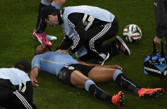 Uruguay's midfielder Alvaro Pereira (down) receives medical assistance after colliding with England's midfielder Raheem Sterling during a Group D football match between Uruguay and England at the Corinthians Arena in Sao Paulo during the 2014 FIFA World Cup on June 19, 2014.    AFP PHOTO / JUAN BARRETOJUAN BARRETO/AFP/Getty Images