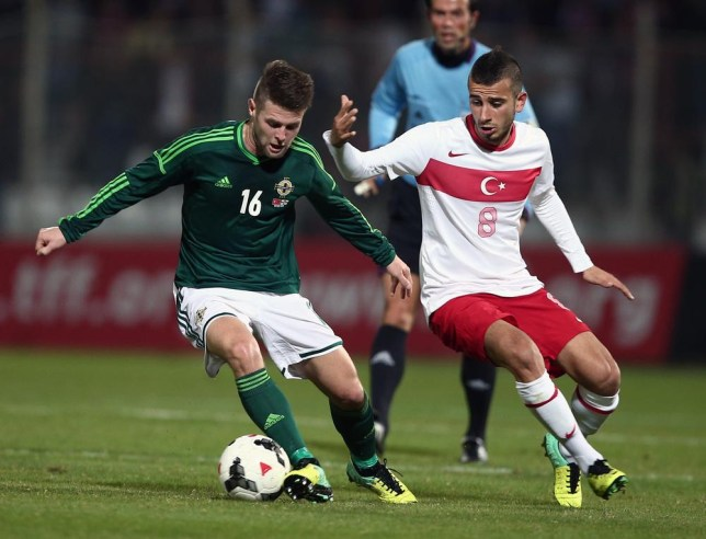 Turkey's Oguzhan Ozyakup, right, and Oliver Norwood of Northern Ireland fight for the ball during their friendly soccer match in Adana, Turkey, Friday, Nov. 15, 2013. (AP Photo) AP Photo