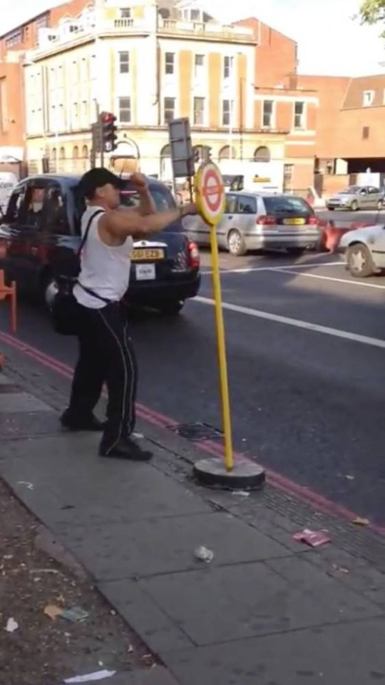 **MANDATORY BYLINE** RAW CUT / CATERS NEWS - (PICTURED; Drunk man fighting a bus stop - A DRUNK man fights a bus stop in a hilarious viral video sweeping the internet. The man - who appears to be intoxicated - can be seen ducking, diving and punching the temporary bus stop in North London. Other passengers look on with amazement, before breaking out into laughter when realising the guys harmless fun.