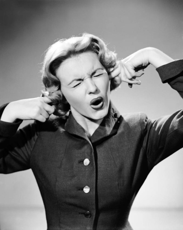 A woman annoyed by a noise. Date unknown. --- Image by   H. Armstrong Roberts/CORBIS