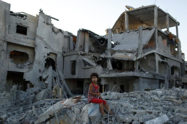 "A girl sits on the ruins of her family's home that witnesses say was destroyed by Israeli airstrikes in the Beit Hanoun neighbourhood of Gaza City, August 12, 2014. Talks to end a month-long war between Israel and Gaza militants are ""difficult"", Palestinian delegates said on Tuesday, while Israeli officials said no progress had been made so far and fighting could soon resume. REUTERS/Siegfried Modola (GAZA - Tags: CONFLICT POLITICS CIVIL UNREST TPX IMAGES OF THE DAY) Siegfried Modola/Reuters"