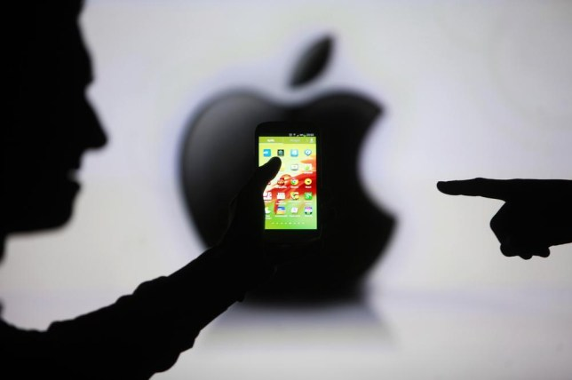 Men are silhouetted against a video screen with an Apple Inc logo as they pose with a Samsung Galaxy S3 smartphone in this photo illustration taken in the central Bosnian town of Zenica, May 17, 2013. Samsung Electronics Co Ltd and Apple Inc agreed to scale down their international legal war and withdraw patent lawsuits outside the United States, a Samsung spokesman said on August 6. REUTERS/Dado Ruvic/Files (BOSNIA AND HERZEGOVINA - Tags: BUSINESS TELECOMS CRIME LAW SCIENCE TECHNOLOGY) Dado Ruvic/Reuters