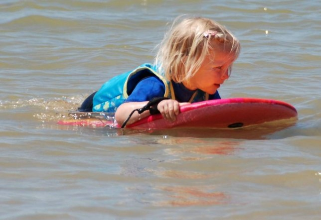 Collect picture. Jemima Chambers, 4, plays in the sea on a previous holiday in Cornwall. May 27 2014.  See SWNS story SWSLEEP: A grateful mother is seeking the hero jet skier who rescued her four-year-old daughter after finding her ASLEEP on a body board - half-a-mile out to sea. Little Jemima Chambers was playing in the shallows during a family holiday with her cousins when she began to drift out to sea on a boogie board. Horrified mum Rebecca raised the alarm then hopped on the back of the mystery saviour's jet ski and sped off around the headland only to find Jemima asleep on the board. The drama unfolded after Rebecca Chambers, 36, and Jemima's aunt Rachel Le Marquand, swam around the harbour at Rozel Bay, Jersey.