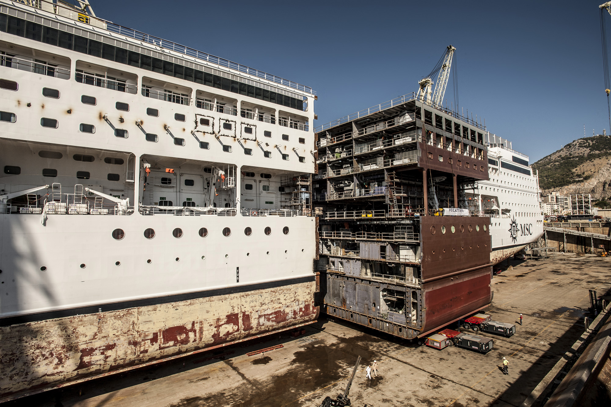 New block on the skids: The new section, dwarfing workers on the quayside, is slotted into place on MSC Armonia (Picture: MSC Cruises)