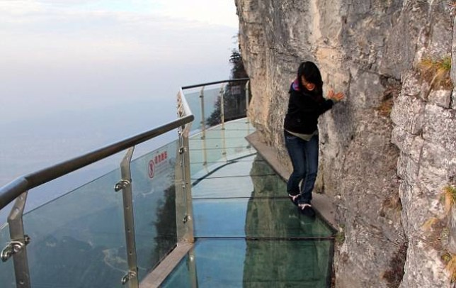 Don't look down! The terrifying see-through path stuck to a Chinese cliff-face 4,000ft above a rocky ravine  Read more: http://www.dailymail.co.uk/news/article-2060023/Chinas-newest-tourist-attraction--glass-bottomed-walkway-cliff-face.html#ixzz3DO8I72TE  Follow us: @MailOnline on Twitter | DailyMail on Facebook