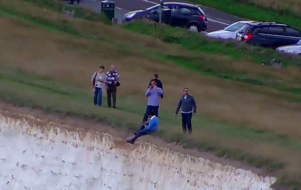 Shocking moment man dangles legs off Beachy Head cliffs for photo