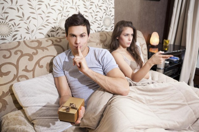 Man doing the 'silence please' gesture with finger on mouth and looking at camera, holding a gift in gold box, while woman is sitting next to him, holding remote control and watching tv rilueda/rilueda