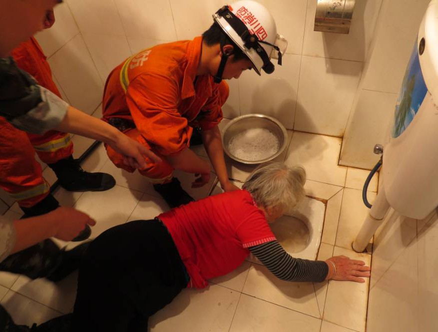 """Mandatory Credit: Photo by XJZ/Quirky China News/REX (4192006c)  Granny Zhang is rescued as emergency workers help to extract her arm from the toilet.  Elderly woman rescued after getting arm stuck in toilet trying to fish out dropped false teeth, Guangyuan, Sichuan, China - 08 Oct 2014  An 85-year-old Chinese granny got her arm stuck in a squatting toilet hole for four hours after she tried to fish up the falling artificial teeth.   """"At around 9am, I was washing my artificial teeth in the bathroom, and the teeth slipped and fell into the toilet pan and further slid into the hole."""" Zhang said she tried to fish it up as she could see it lying at the bottom of the hole.   However, when she was trying to stand up, she found her arm was tightly stuck in the hole.   Failing to remove her arm, Granny Zhang had to lie on the ground, waiting for her family members to come back.   At 10am, her daughter-in-law came back home, and was shocked to see Zhang lying on the bathroom ground, and arm poking into the toilet pan hole.   After failing to help get the farm out, Zhang's daughter-in-law called local firefighting department for help.   Arrived firemen soothed the granny, and then lubricated her arm with soap water and removed it out after she was stuck there for nearly four hours."""