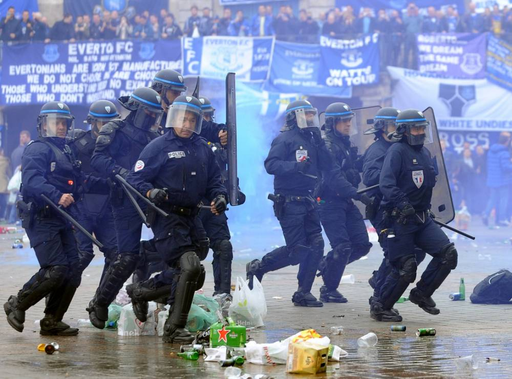 French riot police run as Everton's supporters stand behind their banners on the Grand Place, the main square of the northern French city of Lille, on October 23, 2014, hours before a UEFA Europa League football match Lille-Everton at the Pierre-Mauroy stadium in Villeneuve d'Ascq. AFP PHOTO / FRANCOIS LO PRESTIFRANCOIS LO PRESTI/AFP/Getty Images