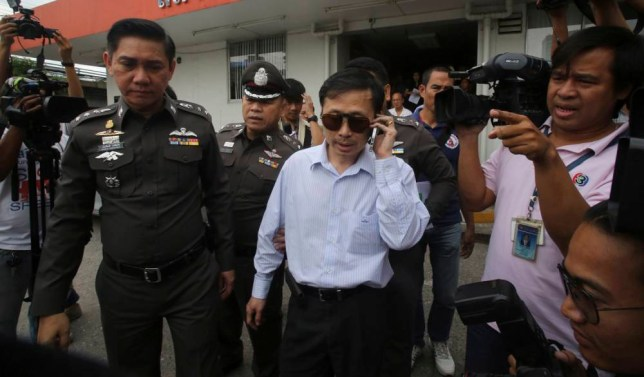 Doctor Sompob Sansiri, center, is escorted by Thai police officers at a police station following his arrest in Bangkok Friday, Oct . 24, 2014, as he faces charges of causing death by reckless endangerment. British woman has died under anesthesia during a cosmetic procedure by Sompob, an uncertified surgeon, at his clinic in Thailand's capital, authorities said Friday. (AP Photo/Sakchai Lalit)