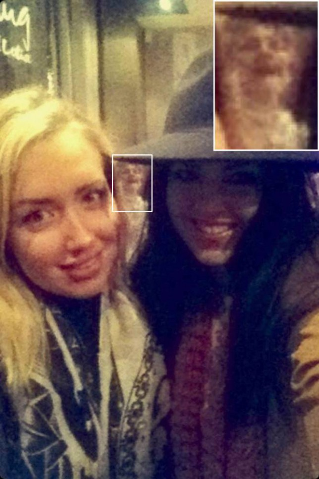 PIC BY MERCURY PRESS (PICTURED: KAYLEY ATKINSON (L) AND VICTORIA GREEVES (R) WITH THE GHOST BEHIND THEM) - These two girls took a selfie and were photobombed by a GHOST. The spooky apparition was caught on camera by pals Victoria Greeves and Kayley Atkinson as they enjoyed a girl's night out in Newcastle-upon-Tyne on Sunday evening. Kayley, 23, and Victoria, 22, had been enjoying a drink at the Slug and Lettuce pub on the Quayside and said the bar was virtually empty when they took the picture. But after striking their best post for a selfie together the girls noticed there was a third person in the photo - which seemed to be an elderly lady dressed in Victorian clothing.Horrified by the chilling figure which seemed to be peering between the glammed up girls, Victoria, who works as a nurse, deleted the spine tingling photo from her phone...SEE MERCURY COPY