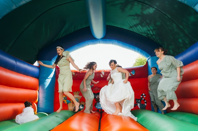 A bride and her bridesmaids jump on a bouncy castle at a wedding reception