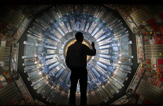 A visitor takes a photograph of an large back lit image of the Large Hadron Collider (LHC) at the Science Museum's 'Collider' exhibition on November 12, 2013 in London, England. At the exhibition, which opens to the public on November 13, 2013 visitors will see a theatre, video and sound art installation and artefacts from the LHC, providing a behind-the-scenes look at the CERN particle physics laboratory in Geneva. It touches on the discovery of the Higgs boson, or God particle, the realisation of scientist Peter Higgs theory. LONDON, ENGLAND - NOVEMBER 12: (Photo by Peter Macdiarmid/Getty Images)