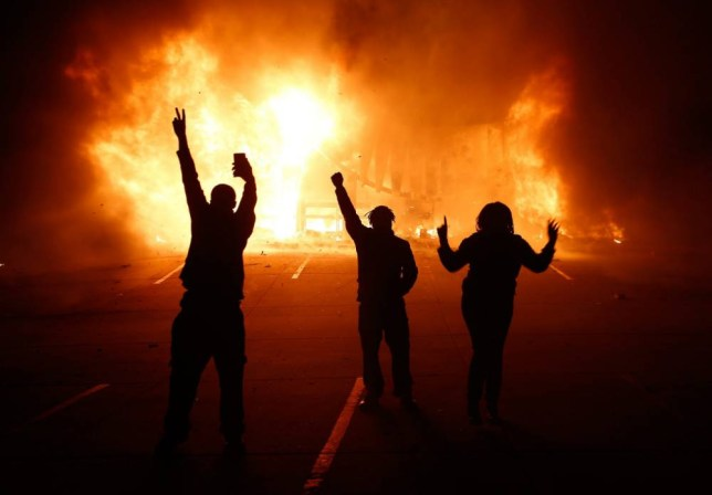 epa04502811 Protesters gesture in front of a burning auto parts store in Ferguson Missouri, USA, 25 November 2014. According to St Louis County Prosecuting Attorney, the Grand jury decided that Ferguson police Officer Darren Wilson will not be charged in the shooting death of unarmed teenager Michael Brown. Protestors have taken to the streets angry that Ferguson police officer Darren Wilson was not indicted by a grand jury for the shooting death of teenager Michael Brown in August 2014.  EPA/TANNEN MAURY