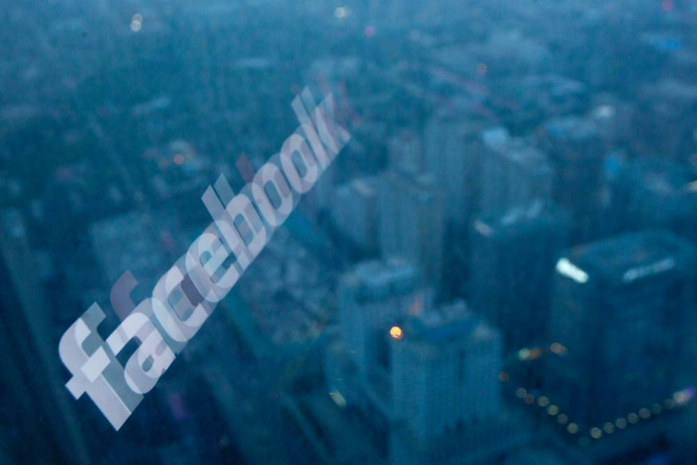 A photo taken on May 16, 2012 shows a computer screen displaying the logo of social networking site Facebook reflected in a window before the Beijing skyline. With investors hungry for Facebook shares ahead of a hotly anticipated offering, the social network unveiled a 25 percent increase in the number of shares to be sold at the market debut. AFP PHOTO / Ed Jones        (Photo credit should read Ed Jones/AFP/GettyImages)