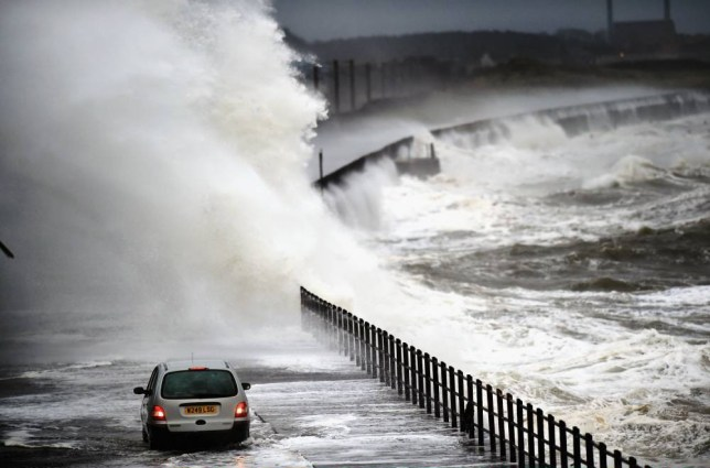 SALTCOATS, SCOTLAND - DECEMBER 09:  A car drives along Seaview road as waves crash over the promenade on December 9, 2014 in Saltcoats ,Scotland. The Met Office has issued a yellow weather warning for the next forty eight hours as high winds start to build ahead of an Atlantic storm due tomorrow.  (Photo by Jeff J Mitchell/Getty Images)