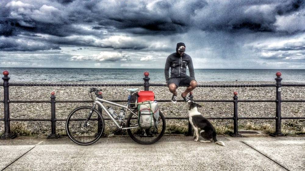 Joshua Sivarajah and his dog Nero pictured on their travels round the world. See SWNS story SWDOG: A adventure loving dog owner has travelled the length and breadth of the UK on a specially adapted bike -- with a seat on the back for his beloved pet. Brave Joshua Sivarajah, 34, decided to leave behind life as he knew it in summer this year, swapping his house for a bike. His loyal collie dog, Nero, joined him on the venture but on the first day of the journey he suffered serious burns to his paws.  Determined not to leave the dog behind, Josh, from Southampton, found a welder who created a shelf on the back of the bike for Nero to sit on.