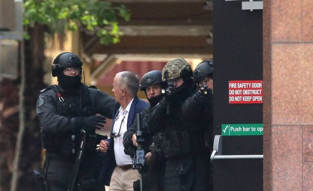 SYDNEY, AUSTRALIA - DECEMBER 15:  A hostage runs to safety outside the Lindt Cafe, Martin Place on December 15, 2014 in Sydney, Australia.  Police attend a hostage situation at Lindt Cafe in Martin Place.  (Photo by Mark Metcalfe/Getty Images)