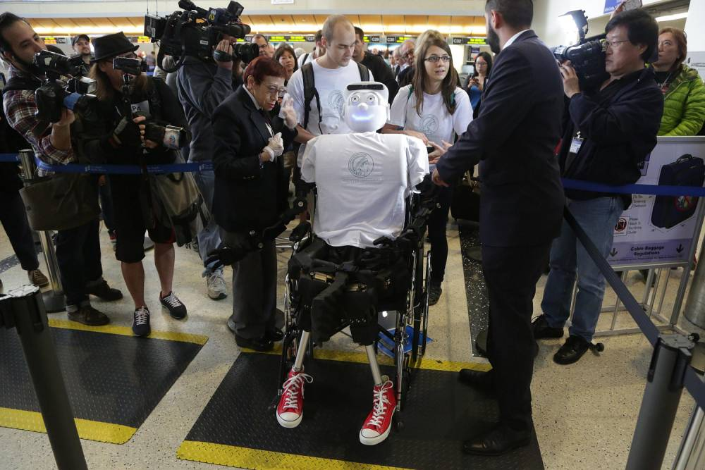 Alexander Herzog (L) and Jeannette Bohg, doctoral student and senior research scientist at Max Planck Society respectively, push 'Athena', the first 'humanoid' robot to fly as a passenger, as  they arrive at Los Angeles International Airport, California December 15, 2014. REUTERS/Jonathan Alcorn (UNITED STATES - Tags: SOCIETY SCIENCE TECHNOLOGY TRANSPORT)