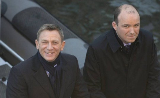 Actors Daniel Craig, left, and Rory Kinnear smile for photographers as they film a scene for the new James Bond film, Spectre, in London, Tuesday, Dec. 16, 2014. (AP Photo/Alastair Grant)