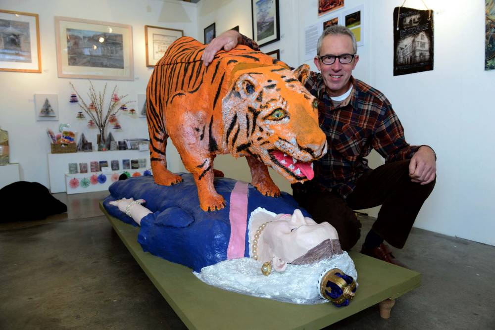 """Artist Bill Sample, with his controversial sculpture of Queen Victoria being attacked by a tiger. See News Team story NTITIGER;  A controversial sculpture has been banned by the National Trust because it shows Queen Victoria being pounced on by a full-sized TIGER. Artist Bill Sample came up with the quirky artwork to symbolise British rule of colonised India. The 61-year-old made the piece - called Tipu's Revenge - for an exhibition at medieval Powis Castle near Welshpool in mid-Wales. But bosses at the National Trust property turned the sculpture down because they thought it was unsuitable for an institution with a """"strong Royalist tradition""""."""