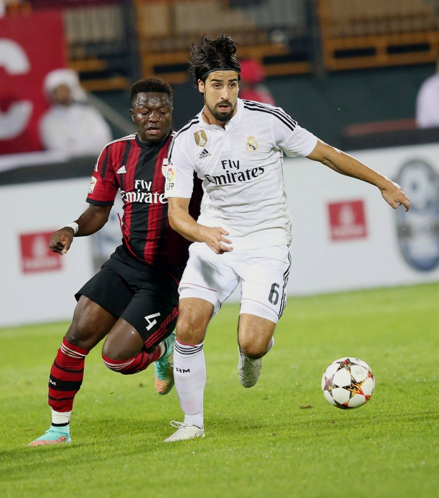 epa04543080 Real Madrid's player Sami Khedira (R) fights for the ball with AC Milan's player Sulley Ali Muntari  (L) during their soccer match of Dubai Football Challenge Cup 2014 at the Sevens stadium in Dubai, United Arab Emirates on 30 December 2014.  EPA/ALI HAIDER
