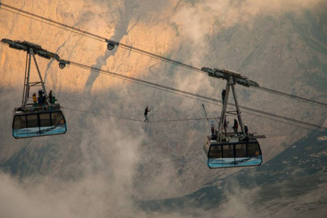 Watch daredevils slackline between two rocking cable cars 500 feet up