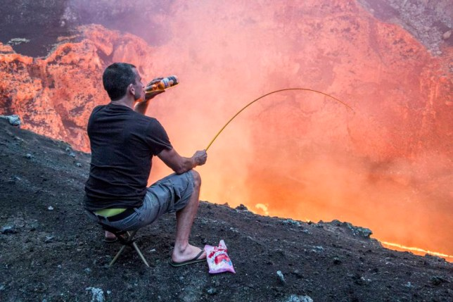 PIC BY BRADLEY AMBROSE / CATERS NEWS - (PICTURED: Simon drinking a beer, whilst roasting a marshmallow over the lava) - A daredevil has taken roasting on an open fire to a whole new level - heating up his marshmallows over a VOLCANO. Brave Bradley Ambrose filmed colleague Simon Turner as the two descended towards a lava lake inside Marcum Crater in Ambrym, Vanuatu. Simon, from Christchurch, New Zealand, wanted to make the trip more memorable so brought a bottle of beer and some marshmallows to roast. He used a spare tent peg which he took with him on the 400m deep descent towards the lava lake and temperatures of more than 2000F. A seasoned volcano expert, Bradley has made the descent towards the lava lake 12 times in the past - almost three miles of rappelling. SEE CATERS COPY