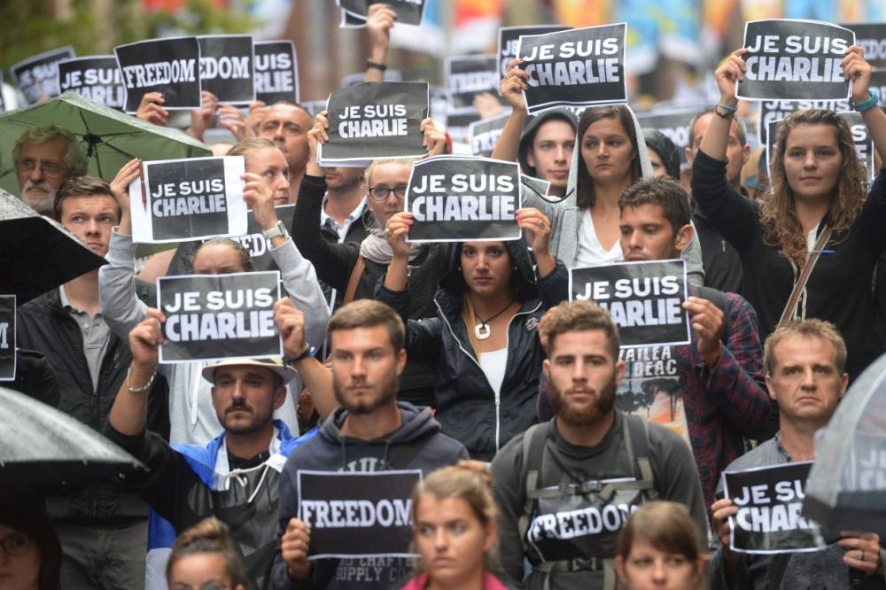 """Members of Sydney's French community gather in the heart of the city to pay tribute to the Paris jihadist attack victims, just meters from the scene of a deadly cafe siege last month in Sydney, on January 11, 2015. Hundreds of people linked hands and displayed """"Je Suis Charlie"""" and """"Freedom"""" placards as they paid their respects, led by French ambassador Christophe Lecourtier, marching in silence down Martin Place during the """"No fear, no freedom"""" rally, despite persistent rain. AFP PHOTO/Peter PARKSPETER PARKS/AFP/Getty Images"""